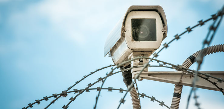 Jaily yard security camera on top of razor wire fence