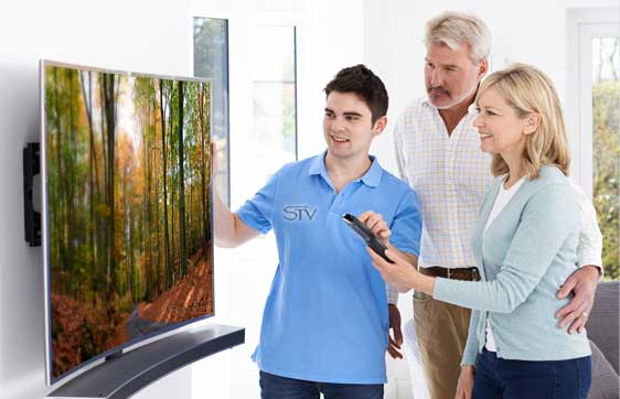 Smiling STV Technician showing man and woman how to use flat screen TV remote control