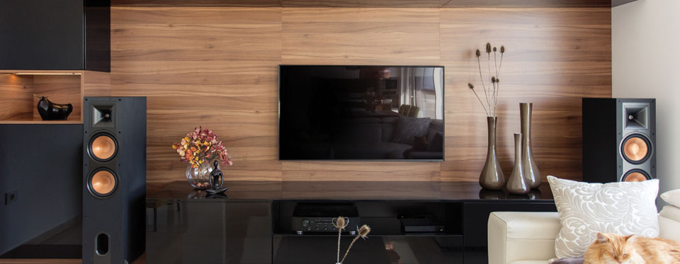 Wall-mounted TV, flanked by speakers.